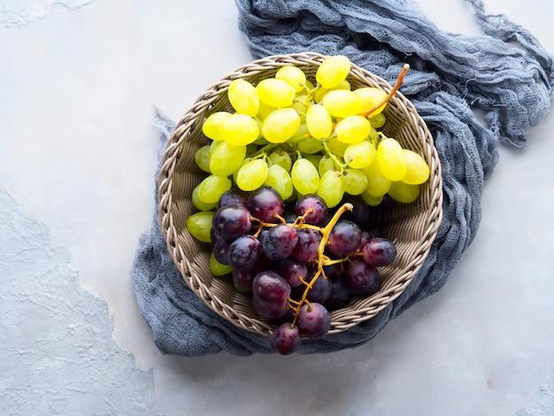 Uvas blancas y oscuras en una canasta