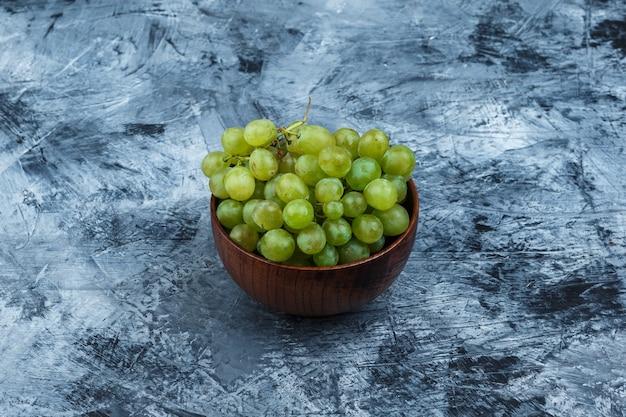 Uvas blancas en un recipiente de cerca sobre un fondo de mármol azul oscuro