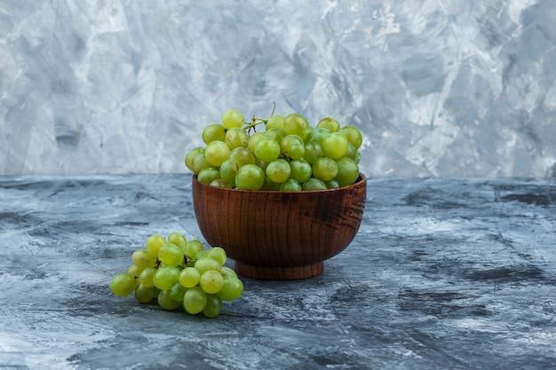 Uvas blancas en un recipiente sobre un fondo de mármol azul claro y oscuro. de cerca.