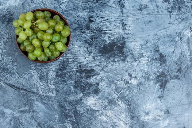 Uvas blancas en un recipiente sobre un fondo de mármol azul oscuro. endecha plana.