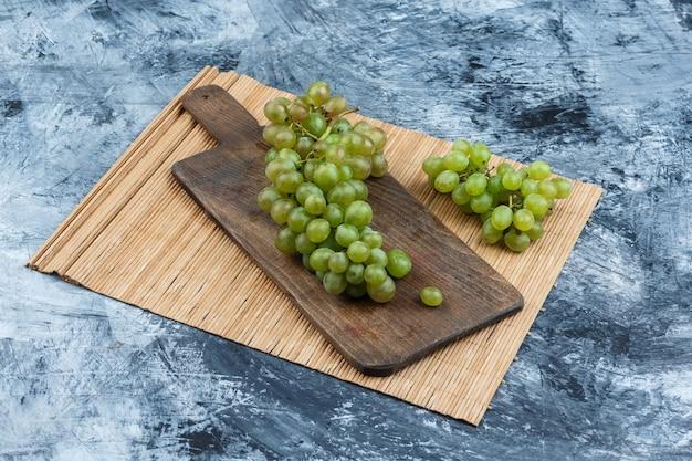 Uvas blancas sobre una tabla de cortar con un alto ángulo de vista de mantel sobre un fondo de mármol azul oscuro
