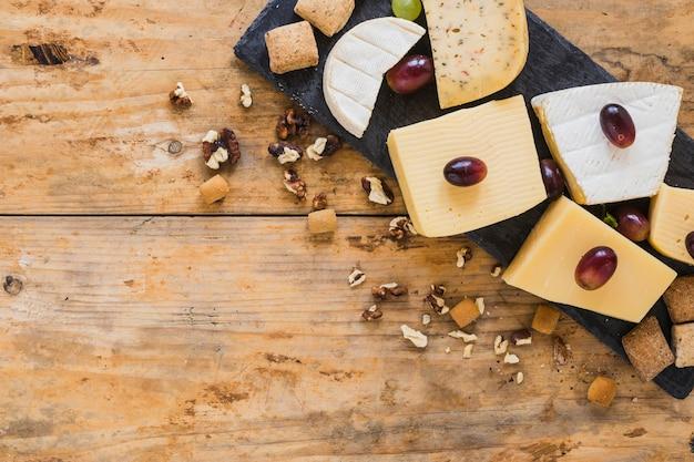 Uvas en bloques de queso con frutos secos en mesa