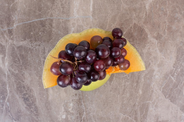 Uvas con calabaza amarilla sobre mesa de mármol