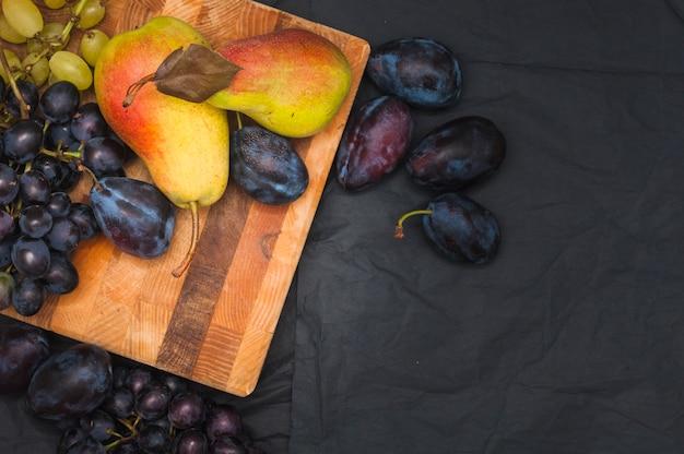 Uvas; ciruela; peras en tabla de cortar de madera