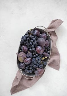 Uvas frescas, ciruelas e higos en un plato, fondo claro