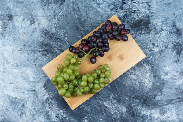 Uvas frescas laicas planas sobre yeso sucio y fondo de tabla de cortar. horizontal
