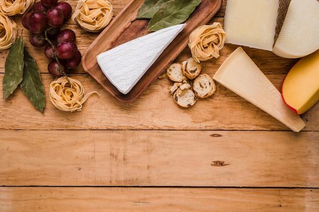 Uvas frescas; pastas; queso y hojas de laurel en mostrador de madera