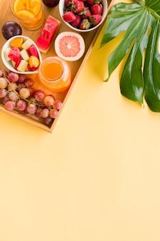 Uvas; jugo; pomelo; sandía; ciruelas fresas en bandeja de madera con hojas de monstera sobre fondo amarillo
