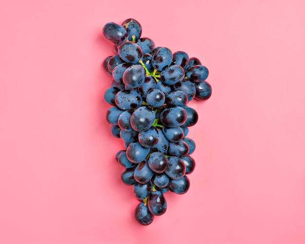Uvas jugosas negras orgánicas naturales en un fondo milenario rosado de la tendencia country village a