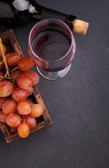 Uvas maduras, vino tinto y una copa sobre un fondo negro