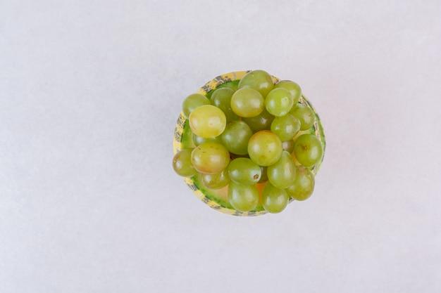 Uvas en medio melón verde cortado sobre superficie blanca