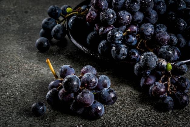 Uvas negras del agricultor orgánico natural crudo, racimos en placa negra, fondo de piedra oscura, copyspace