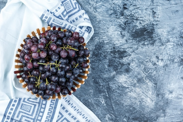 Uvas negras en una canasta plana yacía sobre yeso sucio y fondo de toalla de cocina