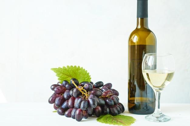 Uvas negras con una copa de vino blanco y una botella de vino en una mesa de luz