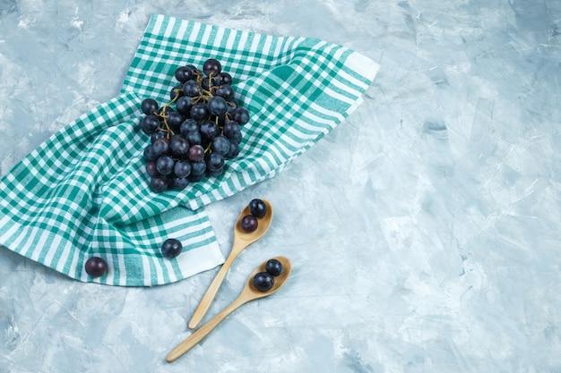 Uvas negras en cucharas de madera sobre fondo gris sucio y toalla de cocina. endecha plana.