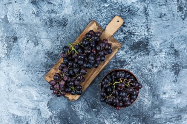 Uvas negras en un cuenco de arcilla sobre yeso sucio y fondo de tabla de cortar. endecha plana.