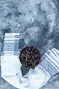 Uvas negras en un cuenco de barro sobre yeso sucio y fondo de toalla de cocina. endecha plana.
