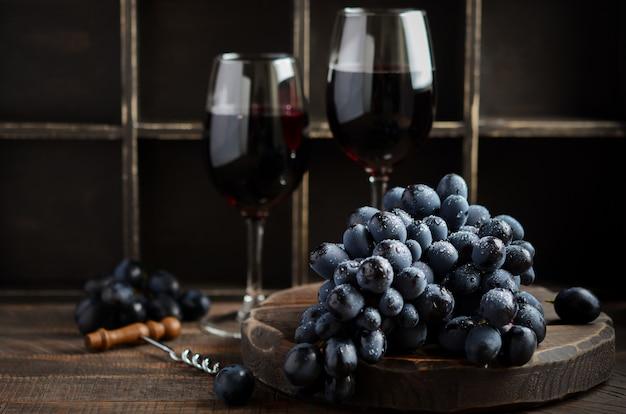 Uvas negras frescas y vino tinto en mesa de madera