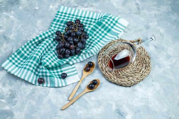 Uvas negras laicas planas en cucharas de madera con una copa de vino, mantel individual sobre yeso y fondo de toalla de cocina. horizontal