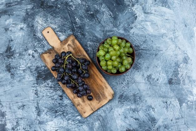 Uvas negras laicas planas sobre una tabla de cortar con un tazón de uvas blancas sobre fondo de mármol azul oscuro. horizontal