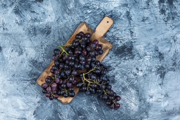 Uvas negras laicas planas sobre yeso sucio y fondo de tabla de cortar. horizontal