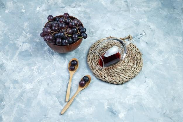 Uvas negras laicas planas en un tazón y cucharas de madera con una copa de vino, mantel individual sobre fondo de yeso gris. horizontal