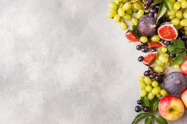 Uvas negras y verdes, higos y hojas sobre una mesa gris.