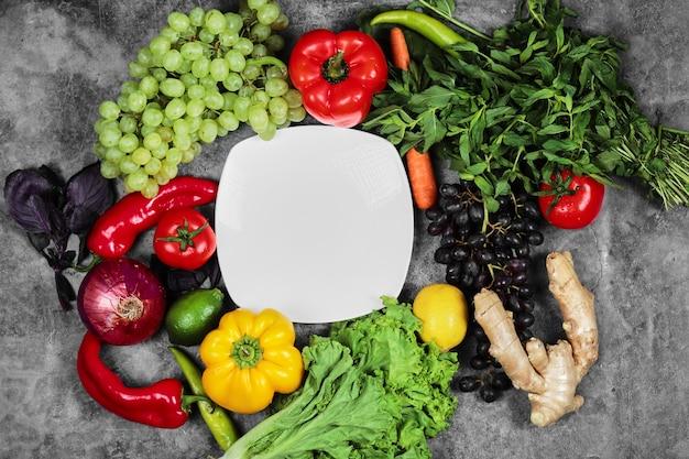Uvas, pimientos, verduras, limón, tomate, jengibre y plato blanco sobre fondo de mármol.