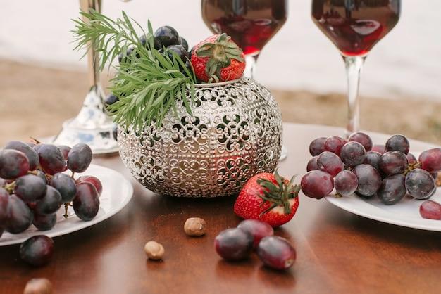 Uvas en platos y esparcidas sobre la mesa, un jarrón plateado en la decoración de un romántico al aire libre