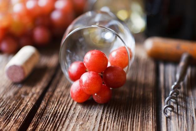 Uvas rojas, copa, botella de vino tinto, corcho y sacacorchos.