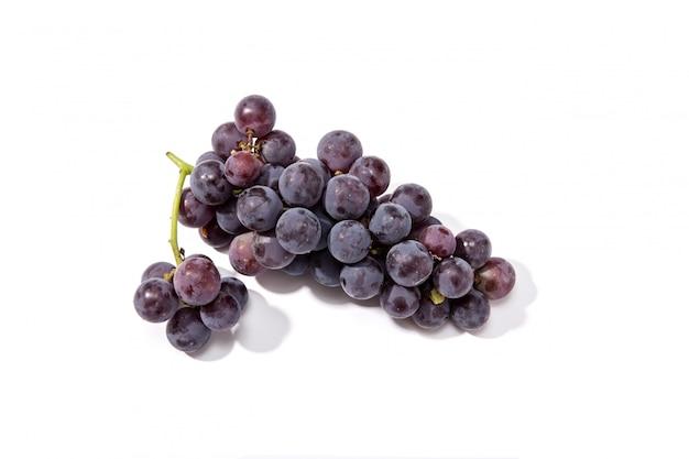 Uvas rojas frescas aisladas sobre fondo blanco.
