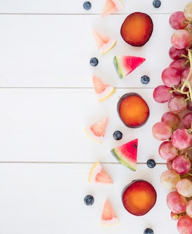 Uvas rojas; rebanadas triangulares de sandía; pomelos y arándanos en el escritorio de madera