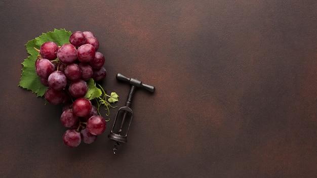 Uvas rojas y sacacorchos de vino.