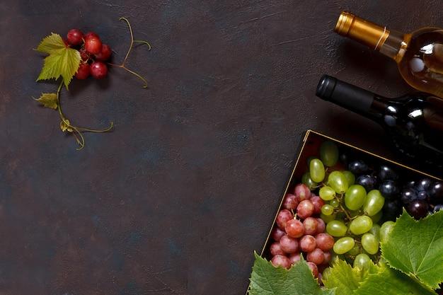 Uvas rojas, verdes y azules con hojas en caja de metal y dos botellas de vino.