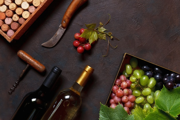 Uvas rojas, verdes y azules con hojas en caja de metal.