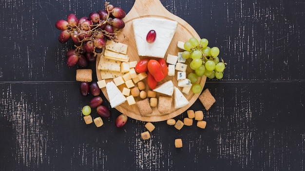Uvas rojas y verdes, tomates, queso y pastelería sobre fondo negro con textura