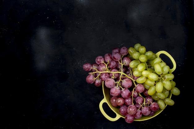 Uvas rosadas y verdes en un recipiente sobre un fondo negro