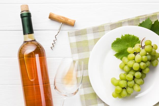 Uvas sobre plato y vino blanco.