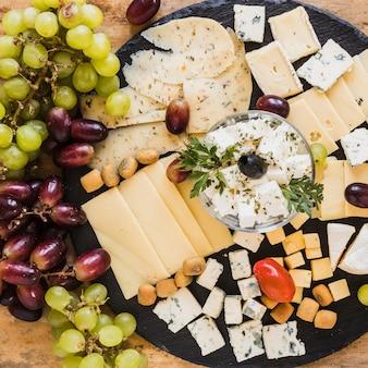 Uvas con variedad de cubitos de queso y rodajas sobre tablero de pizarra negro