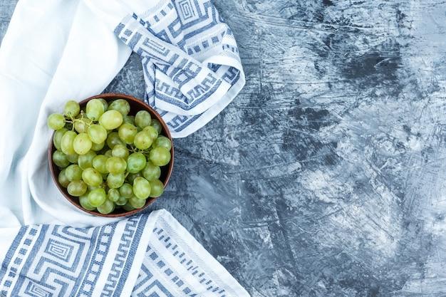 Uvas verdes en un cuenco de barro sobre yeso sucio y fondo de toalla de cocina. endecha plana.