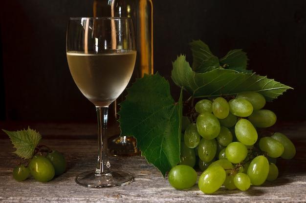 Uvas verdes con hojas, copa, botella de vino blanco.