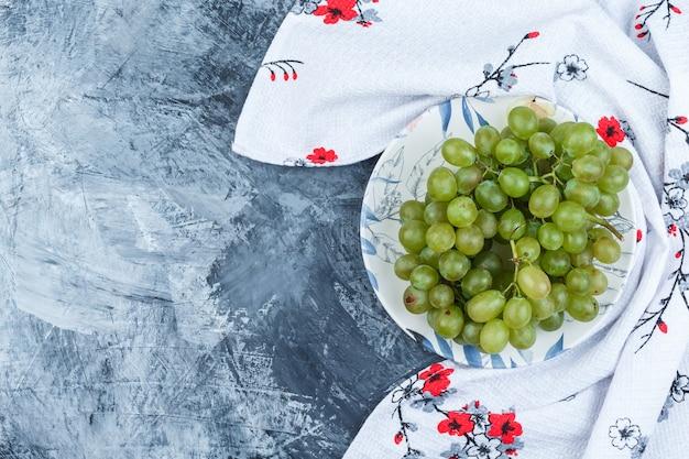 Uvas verdes en un plato sobre yeso sucio y fondo de toalla de cocina. endecha plana.