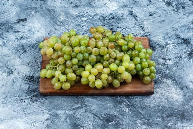Uvas verdes sobre fondo gris sucio y tabla de cortar. horizontal Foto gratis