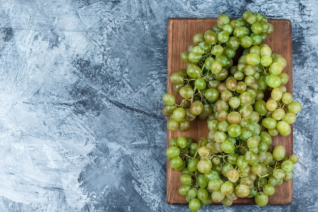 Uvas verdes sobre yeso sucio y fondo de tabla de cortar. endecha plana.