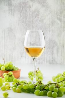 Uvas verdes con vino en copa en un plato de arcilla sobre superficie blanca