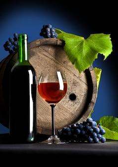 Uvas y vino tinto en botella y vaso.
