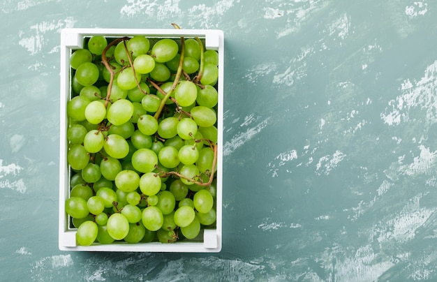 Uvas en una vista superior de la caja de madera sobre un fondo de yeso sucio