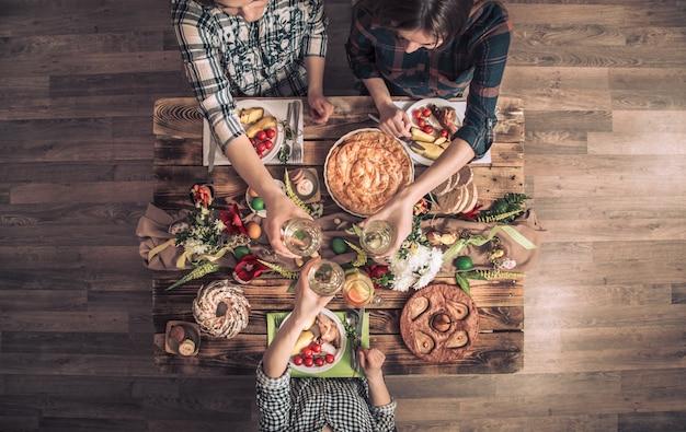 Vacaciones amigos o familiares en la mesa festiva con carne de conejo, verduras, pasteles, huevos, vista superior.