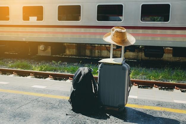 Vacaciones y concepto de viaje. bolsa de viaje, sombrero de paja y mapa en la estación de tren.