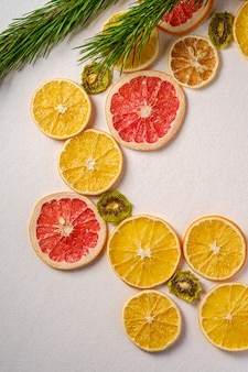 Vacaciones creativas navidad año nuevo alimentos textura de frutas con pomelo seco, kiwi, naranja y limón con rama de abeto, t